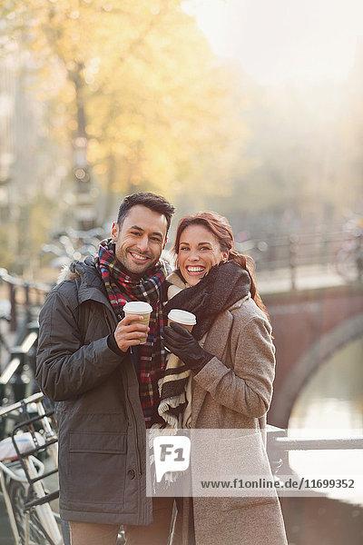 Portrait lächelndes junges Paar beim Kaffeetrinken am städtischen Herbstkanal