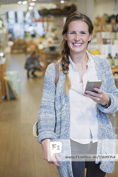Portrait smiling woman texting with cell phone in shop