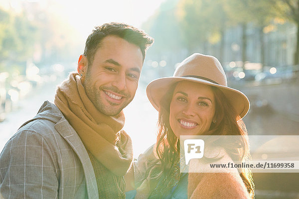 Portrait lächelndes junges Paar am sonnigen Herbstkanal