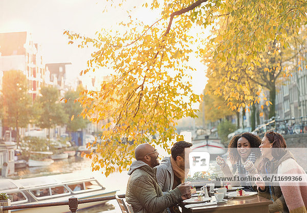 Freunde lachen und essen Käsekuchen Dessert im Herbst Bürgersteig Cafe entlang des Kanals  Amsterdam
