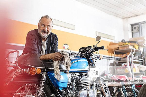 Portrait souveräner Senior-Motorradmechaniker  der sich in der Werkstatt auf das Motorrad stützt