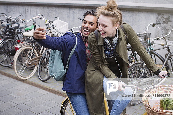 Playful  laughing young couple taking selfie with camera phone on bicycle