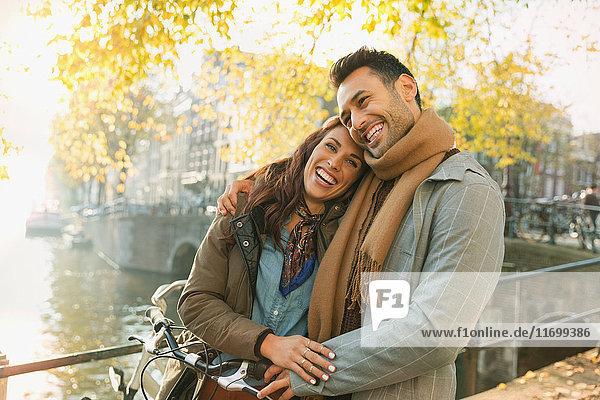 Lachendes junges Paar auf der Herbstbrücke über den Kanal in Amsterdam