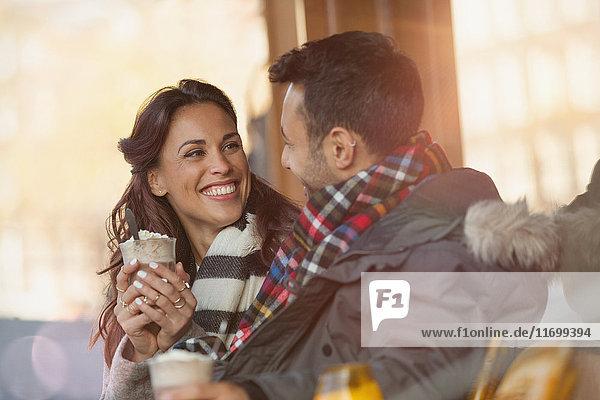 Lächelndes junges Paar trinkt Milchshakes im Straßencafé