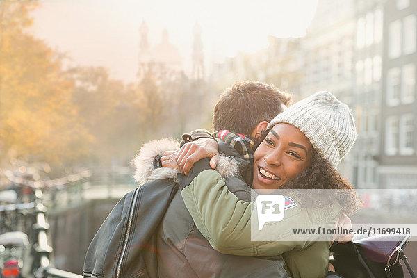Zärtliches junges Paar  das sich in der städtischen Herbststraße umarmt.