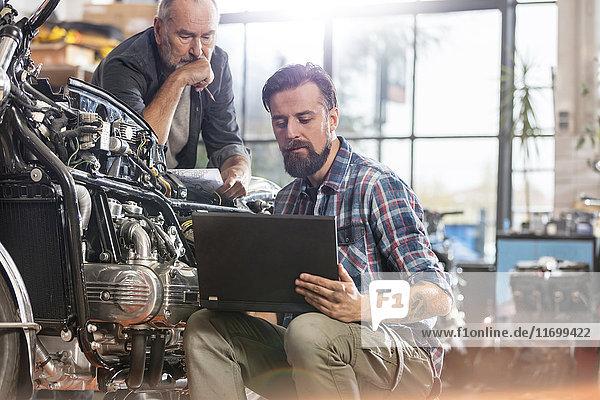 Motorradmechaniker mit Laptop in der Werkstatt