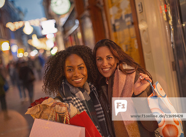 Portrait smiling young women friends with shopping bags on urban night street