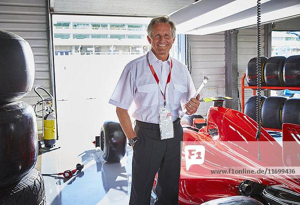 Porträt souveräner Formel-1-Manager neben dem Rennwagen in der Werkstatt