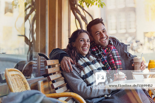 Portrait lachendes junges Paar beim Milchshaken im städtischen Straßencafé