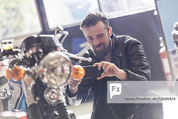 Mann mit Fotohandy fotografiert Motorrad im Geschäft