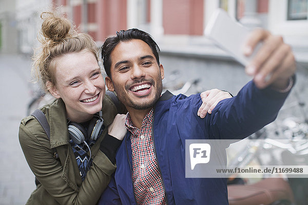 Smiling young couple taking selfie with camera phone