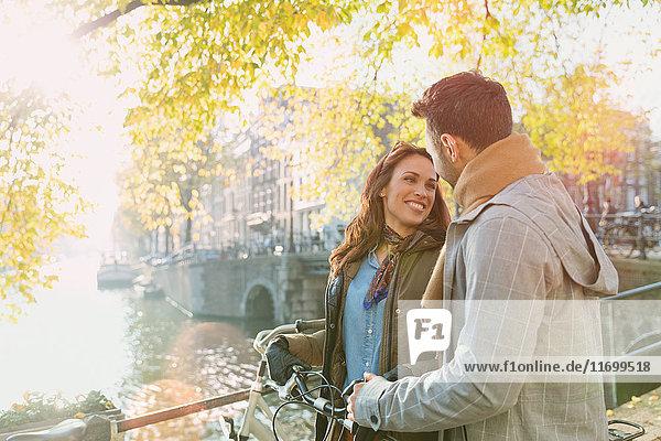Lächelndes junges Paar mit Fahrrad auf der Brücke über den sonnigen Herbstkanal in Amsterdam