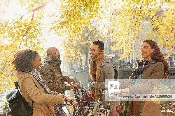 Lächelndes junges Paar Freunde mit Fahrrädern  die sich unter einem sonnigen Herbstbaum unterhalten