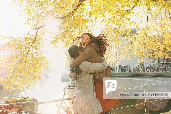 Enthusiastisches Paar am sonnigen Herbstkanal  Amsterdam