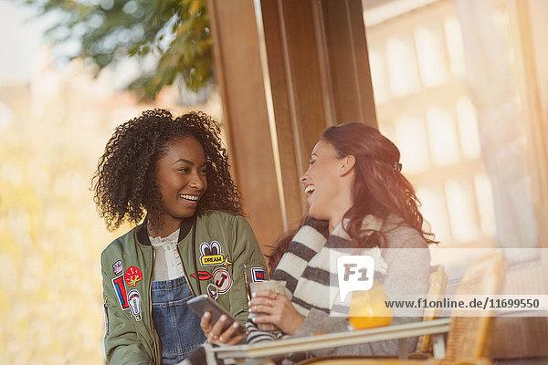 Lachende junge Frauen Freunde mit Handy im städtischen Straßencafé