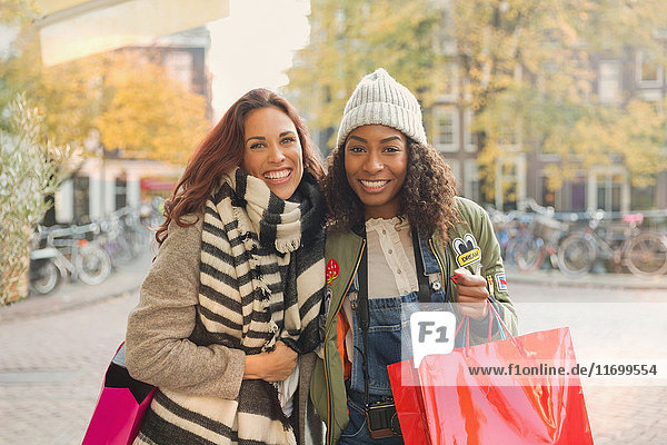 Portrait lächelnde junge Frauen mit Einkaufstaschen auf der urbanen Herbststraße