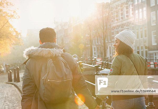Junges Paar hält sich an den Händen und läuft auf der sonnigen Herbststraße  Amsterdam