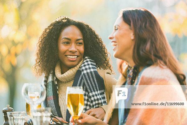 Lächelnde junge Frauen Freunde trinken Bier im Herbst Bürgersteig Cafe
