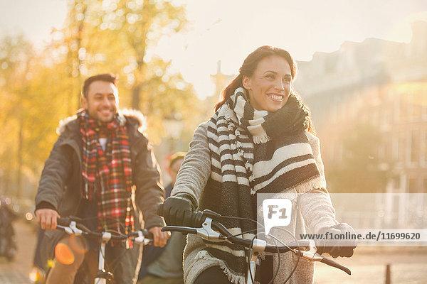 Lächelndes junges Paar beim Radfahren auf der urbanen Herbststraße