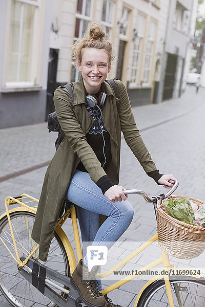 Portrait smiling young woman with headphones riding bicycle with produce in basket