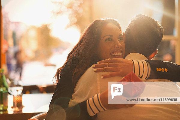 Glückliche Frau  die ein Geschenk erhält und ihren Freund umarmt.