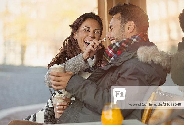 Verspieltes junges Paar mit Milchshake im Bürgersteigcafé