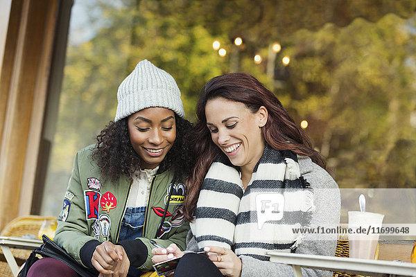 Lächelnde junge Frauen Freunde schreiben Postkarte im städtischen Straßencafé
