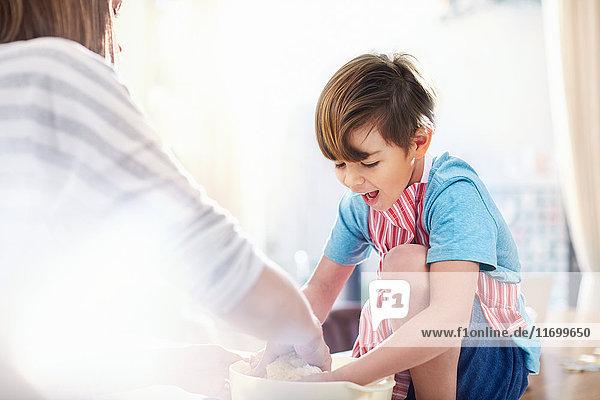 Lächelnder Junge hilft Mutter beim Backen  Teig mischen in der Schüssel