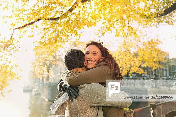 Glückliches Paar am sonnigen städtischen Herbstkanal  Amsterdam