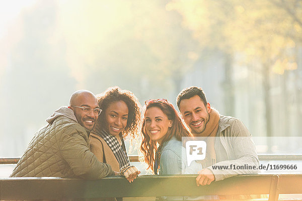 Portrait lächelndes junges Paar Freunde auf sonniger Herbstbank