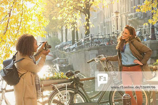 Junge Frau fotografiert Freundin mit Fahrrad am Herbstkanal  Amsterdam