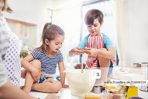 Junge und Mädchen Bruder und Schwester beim Backen auf der Küchentheke