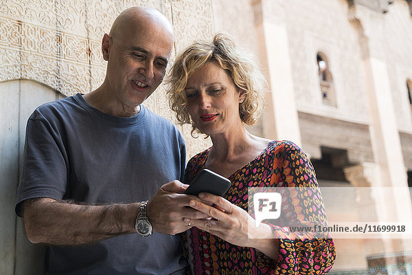 Morocco  Marrakesh  couple looking at cell phone