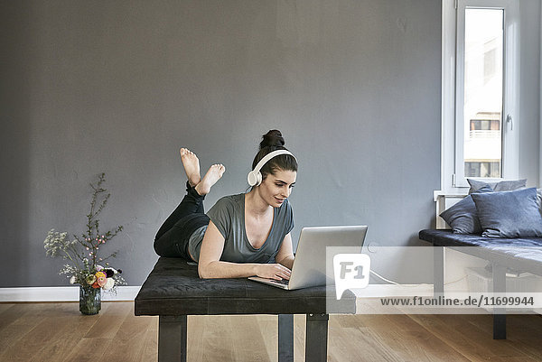 Junge Frau mit Kopfhörer im Wohnzimmer mit Laptop