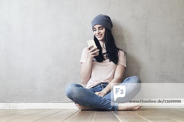 Lächelnde junge Frau auf dem Boden sitzend mit dem Handy
