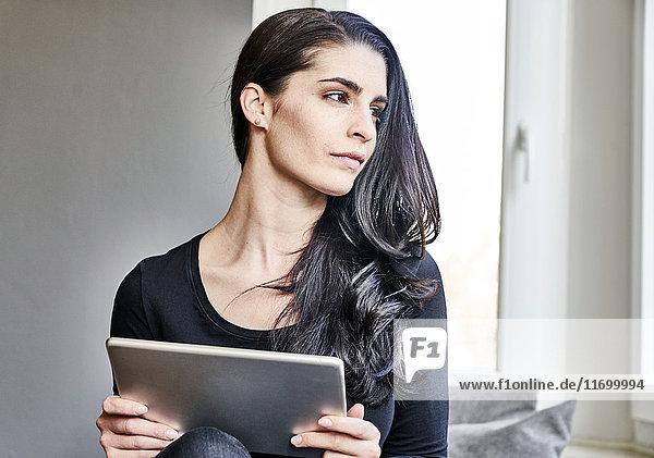 Junge Frau hält Tablette  die zur Seite schaut