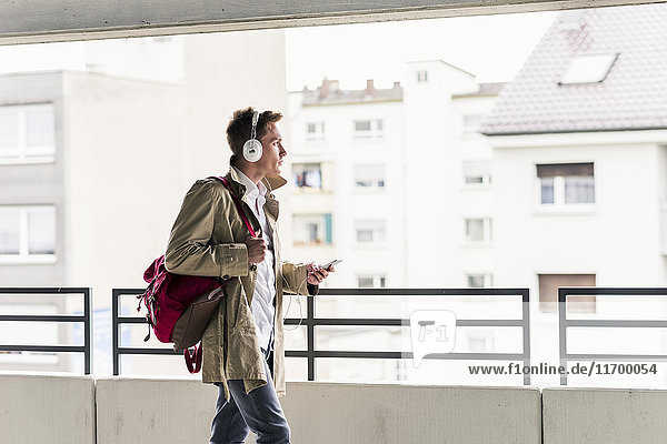 Young businessman using smartphone and headphones
