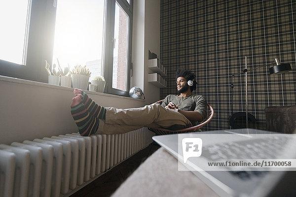 Mann sitzt im Wohnzimmer im Sessel und hört Musik.