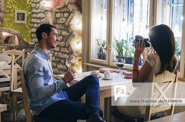 Junges Paar beim Fotografieren in einem Restaurant