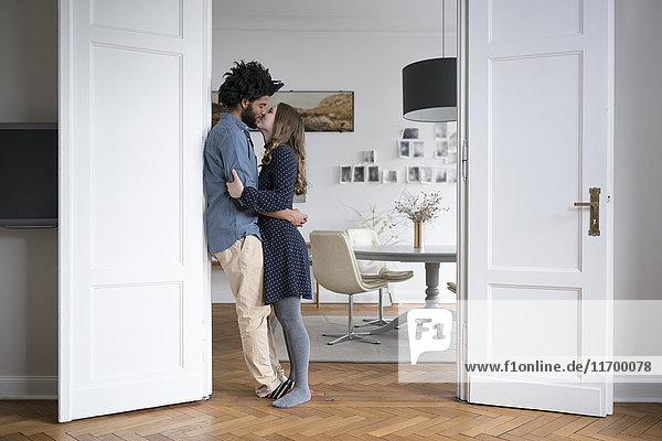Küssendes Paar zu Hause stehend im Türrahmen im Wohnzimmer