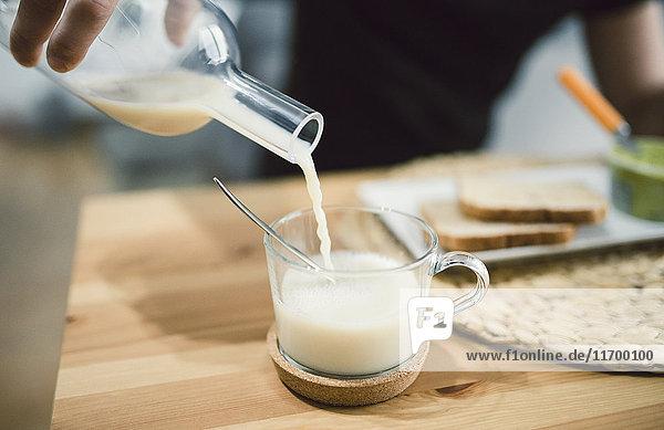 Gießen von Milch in einen Glasbecher