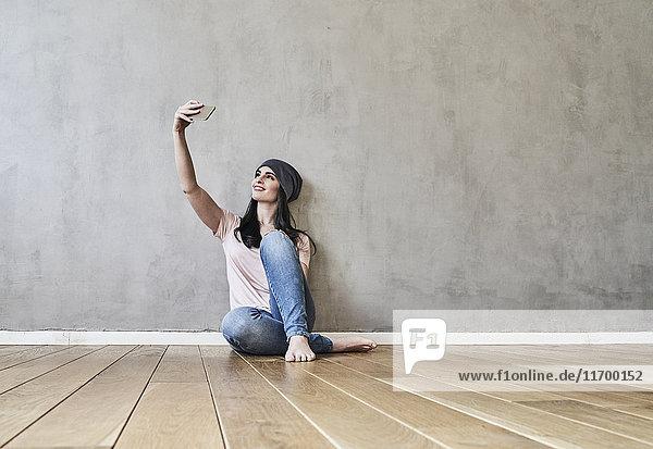 Lächelnde junge Frau sitzt auf dem Boden und nimmt einen Selfie.