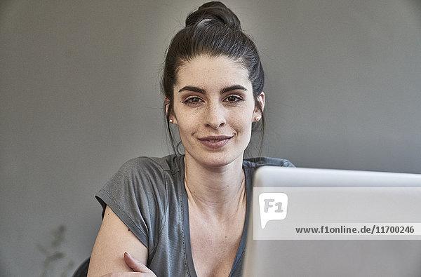 Porträt einer lächelnden jungen Frau mit Laptop
