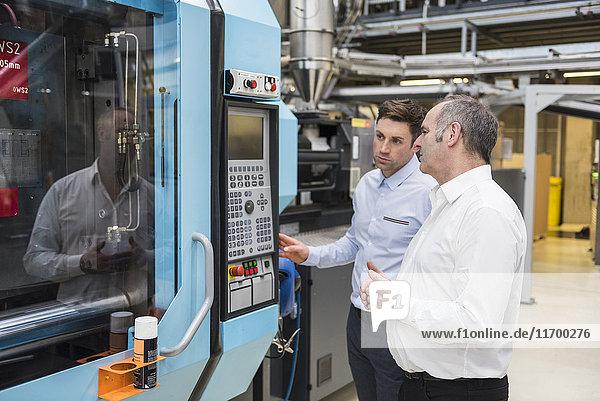 Zwei Männer betrachten die Maschine in der Fabrikhalle