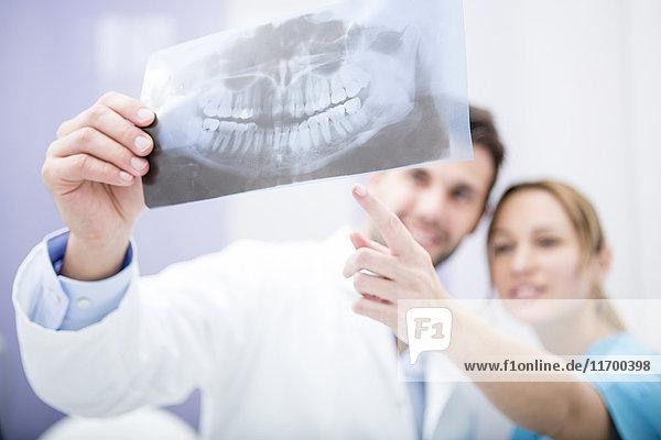 Zwei Ärzte diskutieren über zahnärztliches Röntgenbild