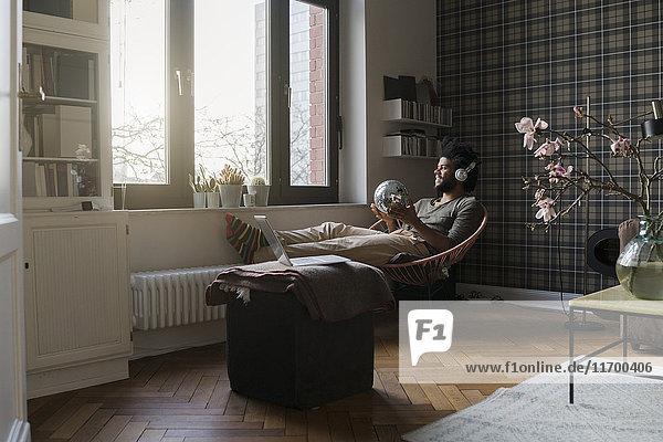 Mann sitzt im Wohnzimmer im Sessel und hält eine Spiegelkugel und hört Musik.