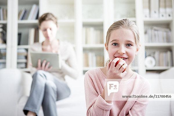 Mädchen beim Apfelessen zu Hause mit Mutter im Hintergrund