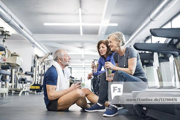 Gruppe von fitten Senioren im Fitnessstudio  die sich nach dem Training ausruhen