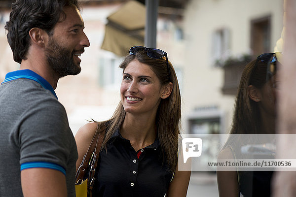 Smiling couple at shop window in a town