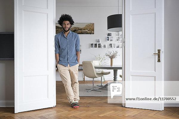 Mann zu Hause stehend im Türrahmen im Wohnzimmer
